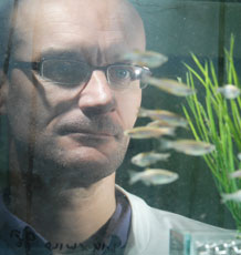 Professor Charles Tyler observing fish in the aquarium